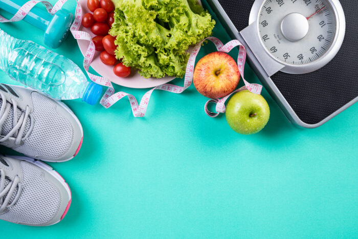 Healthy lifestyle, food and sport concept. Top view of athlete's equipment Weight Scale measuring tape blue dumbbell, sport water bottles, fruit and vegetables on green pastel background.
